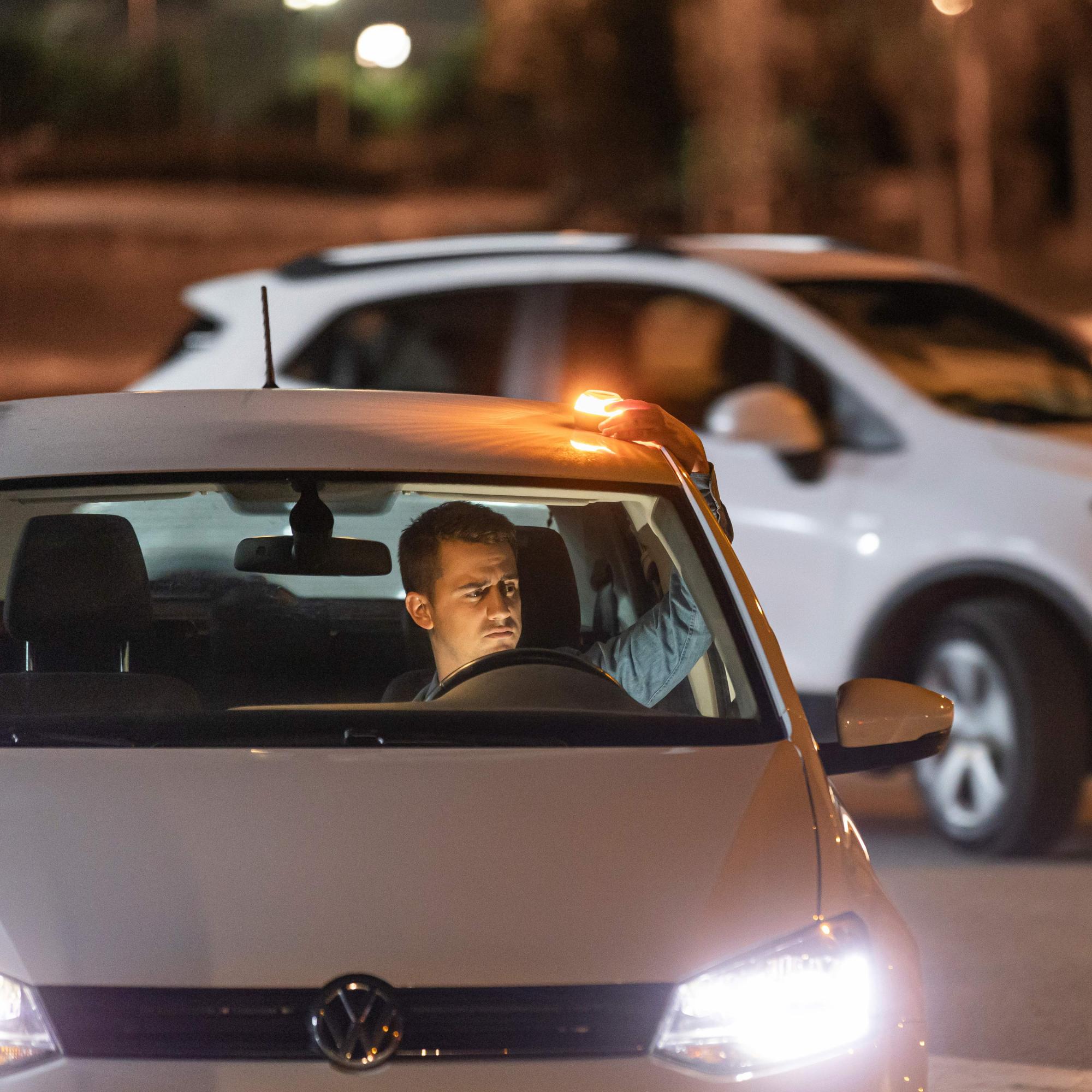 Persona colocando una luz de emergencia para coches modelo SafeLight PRO en el capó de su vehículo.